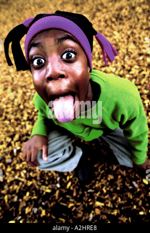 Negro boy age 8-10 pulling tongues into camera. The Image was shot from slightly above. - Stock Photo