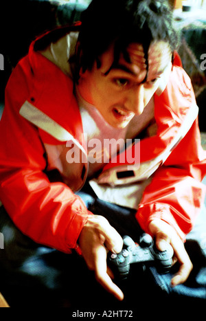 Male age 20-25 playing on a Sony Playstation. - Stock Photo