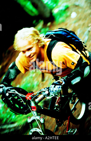 male age 20-25 riding a mountain bike through the woods. The Image shows movement and is in color. - Stock Photo