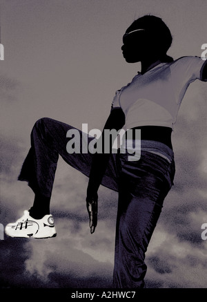 black woman age 20-25 working out against a sky. - Stock Photo
