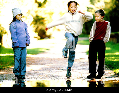 3 children age 6-8 playing in a park, 2 are girls and 1 is a boy. - Stock Photo