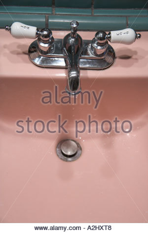 an old style bathroom water tap with dripping water - Stock Photo