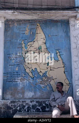 In Stone Town, the small capital of Zanzibar, a man relaxes beneath a Zanzibar map painted on a wall - Stock Photo