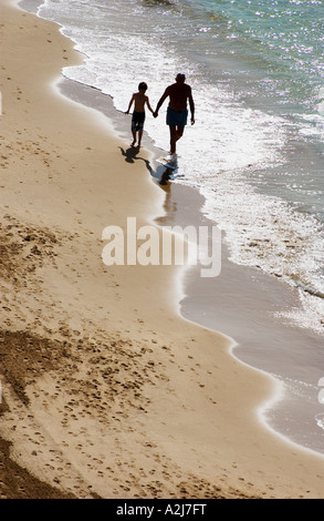 an elderly man takes his grandson for a walk on the beach - Stock Photo