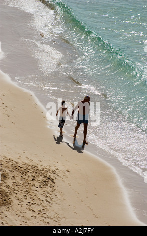 an elderly man takes his grandson for a walk on the beach, holding his hand - Stock Photo