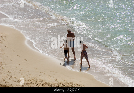 grandfather takes walk on the beach with his two grandsons - Stock Photo