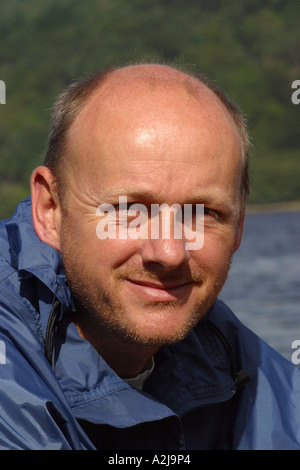 Portrait of bald Middle Age man aged 40 years old with beard stubble in outdoor setting - Stock Photo