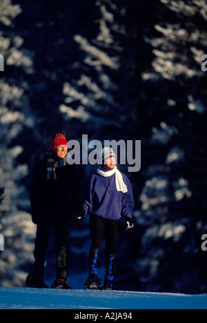 A senior couple in snowshoes peacefully walk hand in hand across a snowy field and look towards the sun low in the - Stock Photo