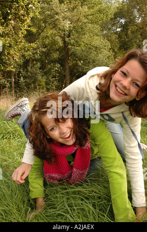 Two teenage sisters romping happily in the grass - Stock Photo