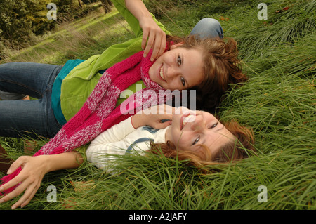 Two teenage sisters merrily frolicking in the grass - Stock Photo