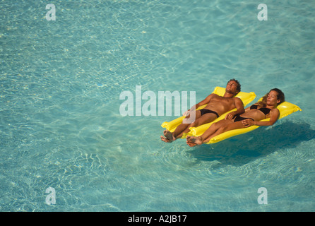 ... Couple Floating Side By Side On Yellow Inflatable Rafts In A Large  Swimming Pool   Stock