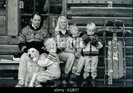 A couple and three children together outside a log cabin on a chilly day drinking warm beverages and playing with - Stock Photo