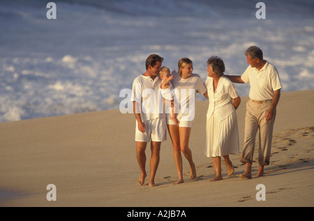 Three generations grandparents parents and young child walking together along the beach - Stock Photo