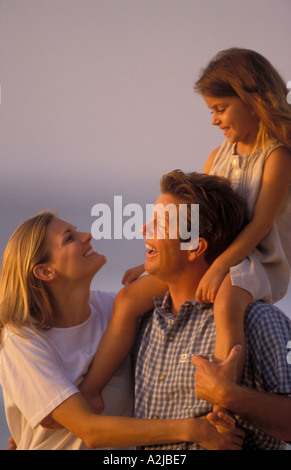 Mother looks up at her daughter being carried on her father shoulders along the beach - Stock Photo
