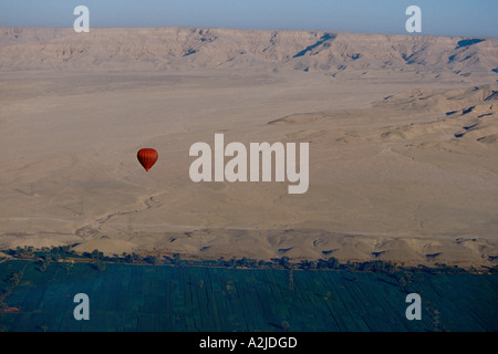 Africa - Egypt - Luxor - Red hot air balloon rises over the West Bank where the fertile farm land meets the desert - Stock Photo
