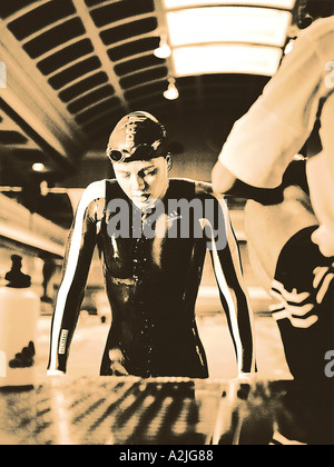 Swimmer,female age 20-25 emerging from a pool with her trainer in the foreground. - Stock Photo