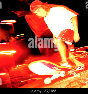 White brazilian male Skateboarder riding a skatepark at night in Brazil with red trailing lights and showing blur - Stock Photo