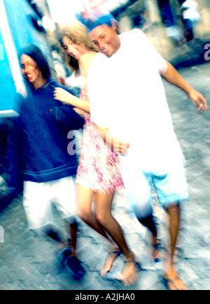 2 teenage boys and 1 teenage girl dancing through a street - Stock Photo