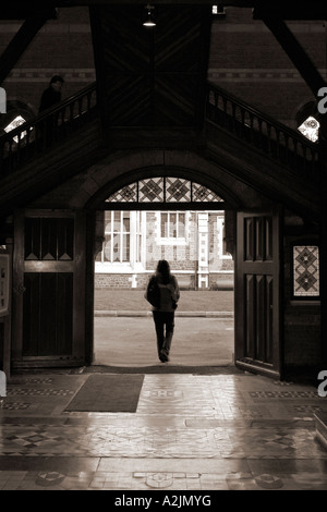 Young woman walking through passageway with lone figure overhead - Stock Photo