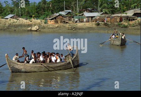 Rowing ferry passengers from Sandwip, an island in the Bay of Bengal, to a waiting ship which will take them to - Stock Photo