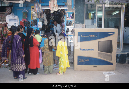 India, Traditionally dressed woman next to a latest model television in Bhuj - Stock Photo