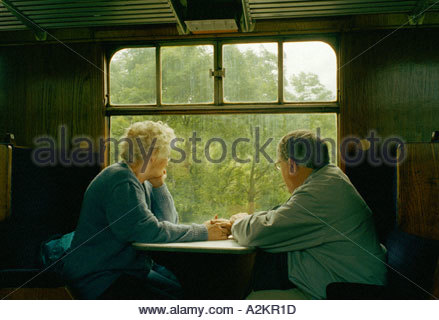 Retired pensioner couple in steam train compartment Glos UK - Stock Photo