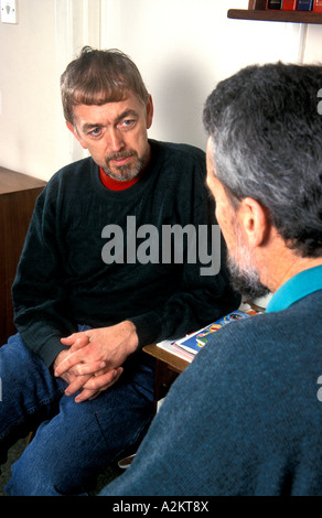 middle aged man in consultation with doctor/counsellor/solicitor/official - Stock Photo
