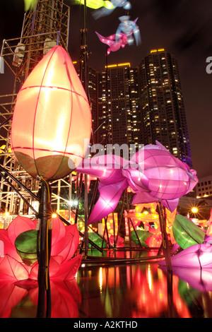 Illuminated lanterns above pond in celebration of Mid Autumn Festival Kowloon Park Tsim Sha Tsui Kowloon Hong Kong - Stock Photo