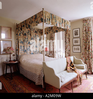 Bedroom with fourposter bed with floral curtains and settee with bolster - Stock Photo