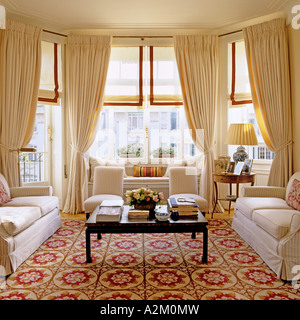 Large living room with three sofas, patterned carpet and bay windows - Stock Photo