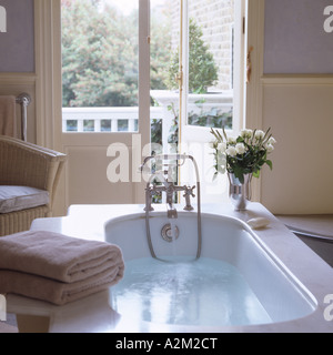 Running bath in bathroom with french doors and balcony - Stock Photo