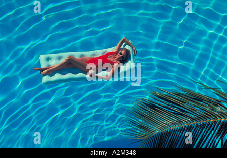 A young woman in a red bathing suit holding a drink while floating on a raft in the crystal blue water of a swimming - Stock Photo