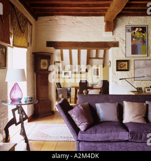 Purple sofa in living room with beamed ceiling and cat-slide roof - Stock Photo