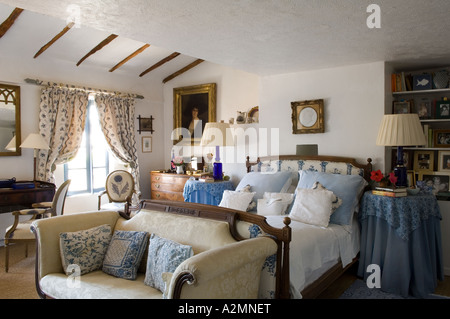 Traditional French country bedroom with sofa in Provençal house - Stock Photo