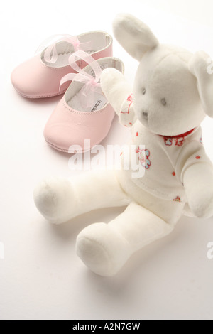 Close-up of pair of baby booties and teddy bear - Stock Photo