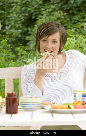 Portrait of young woman having breakfast - Stock Photo
