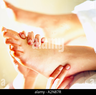 Close-up of woman's hands massaging young woman's foot - Stock Photo
