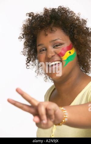 Portrait of young woman with Ghanaian flag painted on her face - Stock Photo