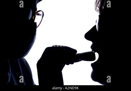 Silhouette of dentist taking a dental impression. Picture by Jim Holden. - Stock Photo