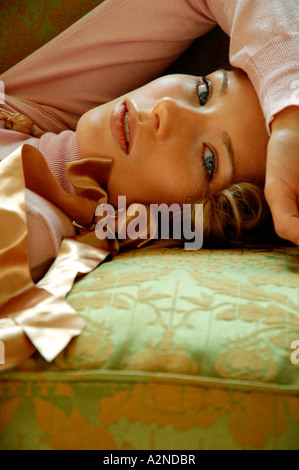 Portrait of young woman lying on bed - Stock Photo