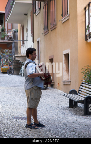 A musician playing accordion on a street in the village of Malcesine on Lake Garda, Italy - Stock Photo