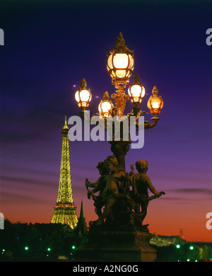 Lamppost and tower lit up at night, Alexandre III Bridge, Eiffel Tower, Paris, France - Stock Photo
