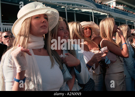 Aintree Racecourse, Liverpool UK.  Young women look on excitedly as the Grand National horse race draws to a close - Stock Photo