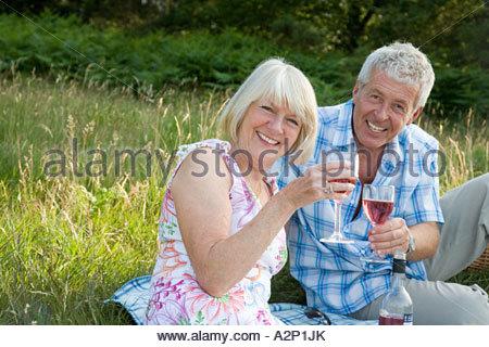 Couple having wine in a field - Stock Photo