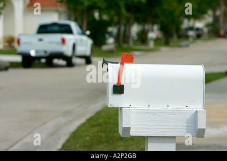 Mailbox letterbox postbox postal correspondence shipping delivery red flag metal esidential close up close-up blue - Stock Photo