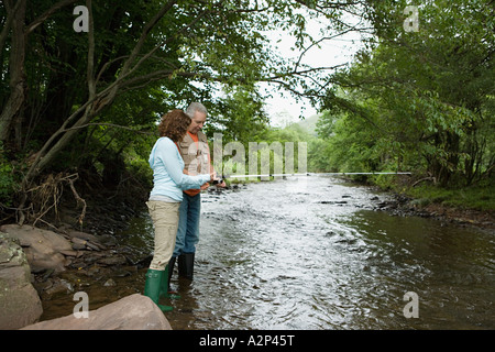 Mature couple fishing in stream - Stock Photo