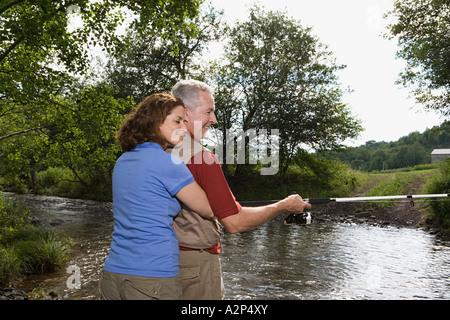 Mature couple fishing in stream - Stock Photo