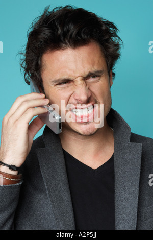 Grimacing man on cellphone - Stock Photo
