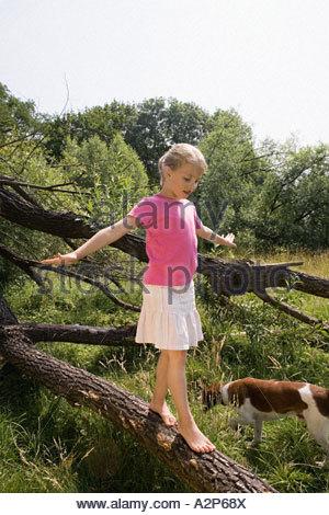 Girl balancing on log - Stock Photo