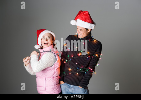 Woman pulling man tied up in christmas lights - Stock Photo